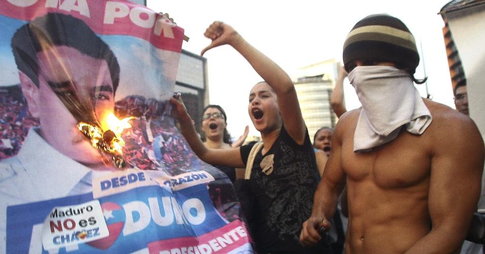 15.abr.2013 - Opositores de Nicolás Maduro queimam imagem do novo presidente venezuelano, durante protesto contra o resultado das eleições nas ruas de Caracas, capital da Venezuela