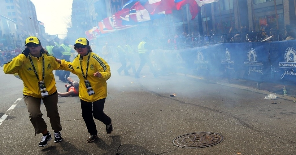 15.abr.2013 - Pessoas correm em meio a fumaça após explosões na Maratona de Boston