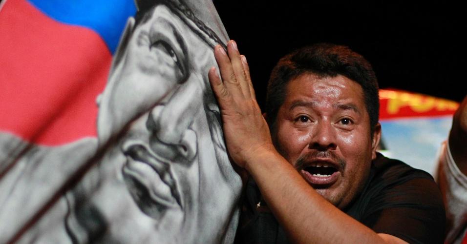 15.abr.2013 - Venezuelano comemora a vitória de Nicolás Maduro, segurando uma imagem de Hugo Chávez, na noite de domingo (14), em San Salvador. Maduro será o sucessor de Hugo Chávez, morto há pouco mais de um mês