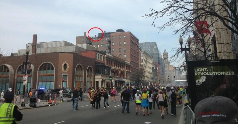 """15.abr.2013 - A publicação no Twitter da foto de um homem no telhado de um prédio (realçado em vermelho) próximo ao local onde ocorreu uma das duas explosões da Maratona de Boston provocou especulações na rede social sobre o possível envolvimento desta pessoa com o ataque. Segundo o site americano """"Slate"""", o FBI diz ter conhecimento da foto, mas não comenta se há alguma suspeita sobre a pessoa que aparece no telhado"""