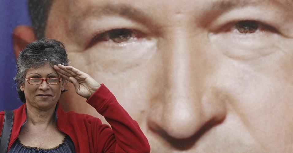 15.abr.2013 - Mulher faz cumprimento em frente a foto do presidente Hugo Chávez durante protestos chavistas em Madri, na Espanha