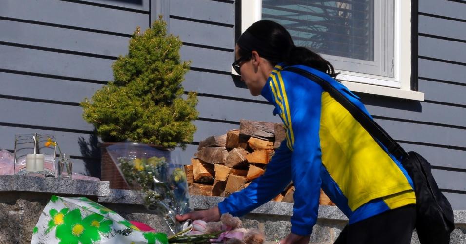 16.abr.2013 - A maratonista Megan Cloke deixa flores na porta de Martin Richard, de oito anos, vítima das explosões na Maratona de Boston, nesta terça-feira (16). Três pessoas morreram nos atentados e 130 ficaram feridas