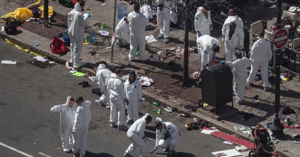 16.abr.2013 - Investigadores usando trajes especiais inspecionam o local onde uma das bombas detonadas durante a Maratona de Boston explodiu. Três pessoas morreram e dezenas ficaram feridas no ataque