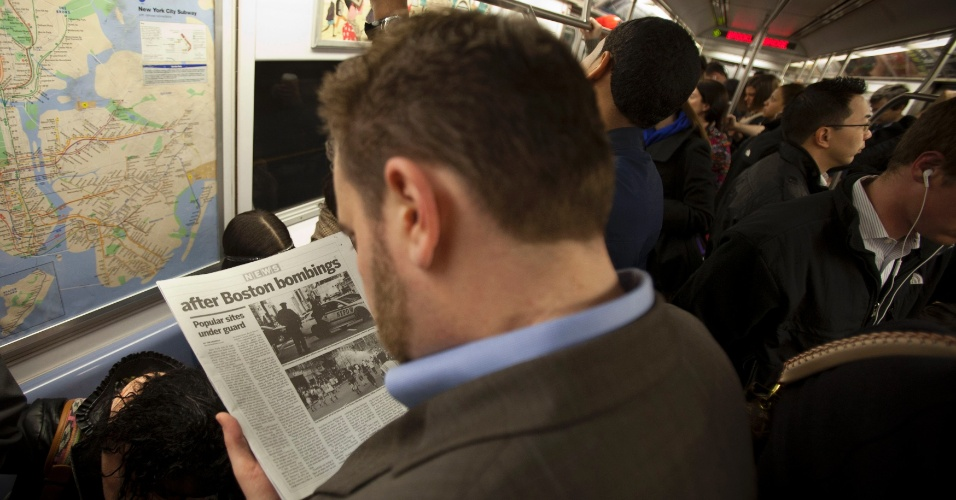 16.abr.2013 - Passageiro lê notícia sobre atentados a bomba em Boston em trem do metrô em Nova York, nesta terça-feira (16). A segurança na cidade foi reforçada