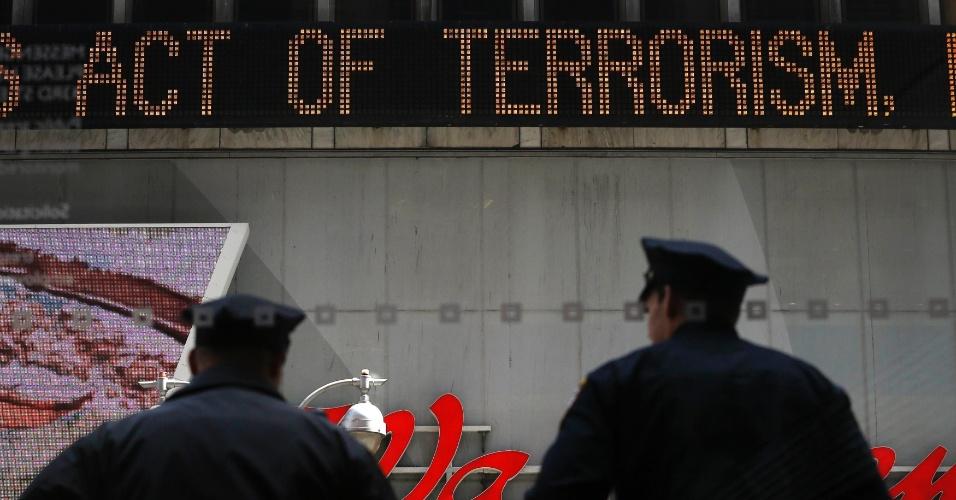 """16.abr.2013 - Policiais param sob letreiro luminoso em Times Square (Nova York) onde se lê """"Ato de terror"""", em inglês. A segurança na cidade americana foi reforçada após o atentado à Maratona de Boston que matou três pessoas e deixou dezenas feridas na segunda-feira (15)"""