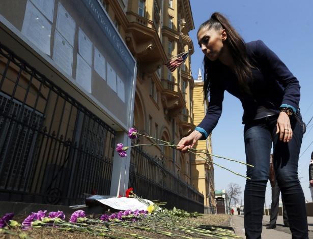 16.abr.2013 - Uma mulher coloca flores diate da embaixada dos Estados Unidos em Moscou, na Rússia, em homenagem às vítimas dos atentados a bomba que ocorreram durante a realização da Maratona de Boston