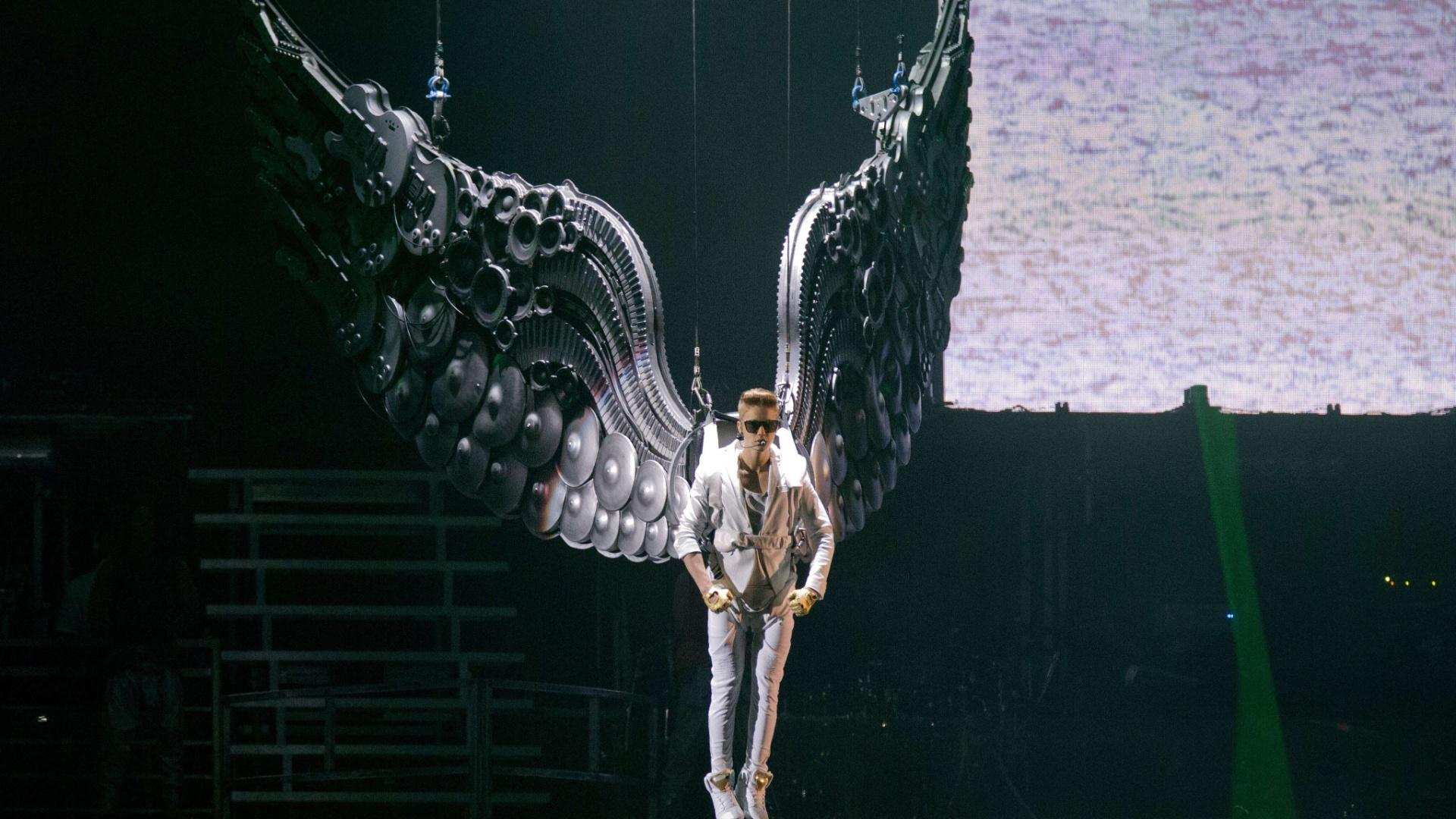 16.abr.2013 - Justin Bieber abre show na Telenor Arena, em Oslo, Noruega, com performance com asas gigantes. As asas são formadas por instrumentos musicais como guitarras e peças como teclas de teclados e pratos de bateria. De branco e óculos escuros, Bieber usa luvas douradas no espetáculo