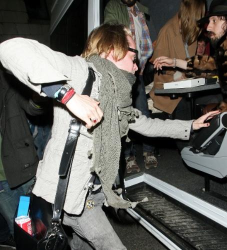 16.abr.2013 - O ator Macaulay Culkin empurra fotógrafos ao sair de uma casa noturna em Brighton, na Inglatera. Ele deixou o local escondendo o rosto com um par de óculos escuros e um cachecol verde