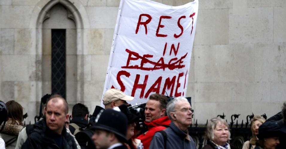 """17.abr.2013 - Cartaz de protesto é erguido entre pessoas que se reúnem em rota de procissão do funeral da ex-primeira-ministra britânica Margaret Thatcher. Em evento raro, a rainha Elizabeth 2ª comparecerá ao funeral da controversa política. No cartaz, lê-se em inglês, fazendo um trocadilho: """"Descanse em vergonha"""""""