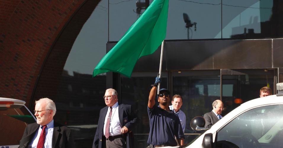 17.abr.2013 - Homem segura uma bandeira verde, sinalizando que é seguro retornar ao prédio do tribunal federal de Boston. Autoridades de segurança haviam determinado nesta quarta-feira (17) que o prédio da corte fosse esvaziado, após uma suspeita de ameaça à segurança