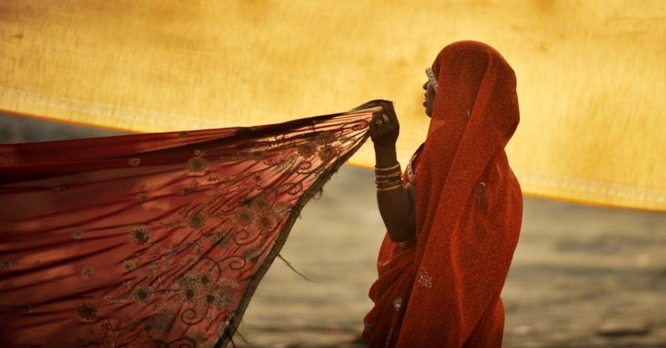 17.abr.2013 - Indiana seca seu sari ao sol depois mergulhar no rio Sangam durante o festival de Navratri em Allahabad, na Índia. O Navratri é um festival que acontece durante nove noites e é realizado em honra da deusa hindu Durga