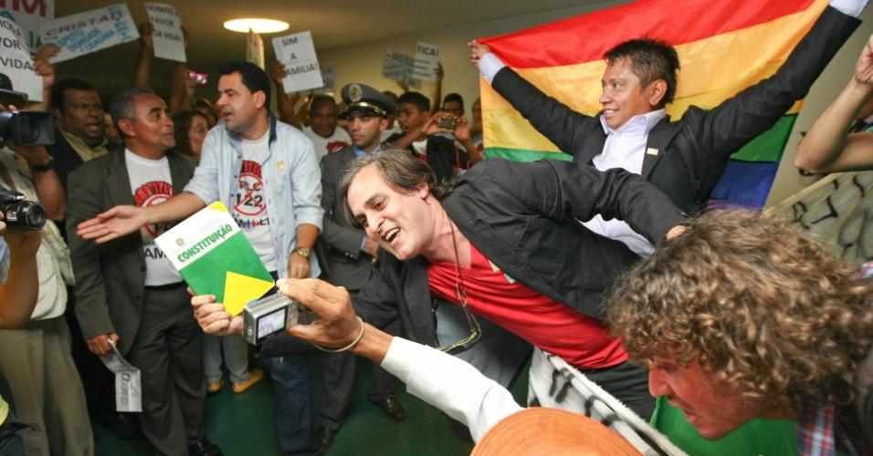 17.abr.2013 - Manifestantes contrários, e outro grupo favorável, à permanência do deputado Marco Feliciano (PSC-SP) na presidência da Comissão de Direitos Humanos da Câmara protestam do lado de fora da sala onde ocorria a sessão do colegiado. Após seguidos protestos tumultuarem as sessões da comissão, Feliciano determinou que a reunião desta quarta-feira (17) fosse fechada ao público