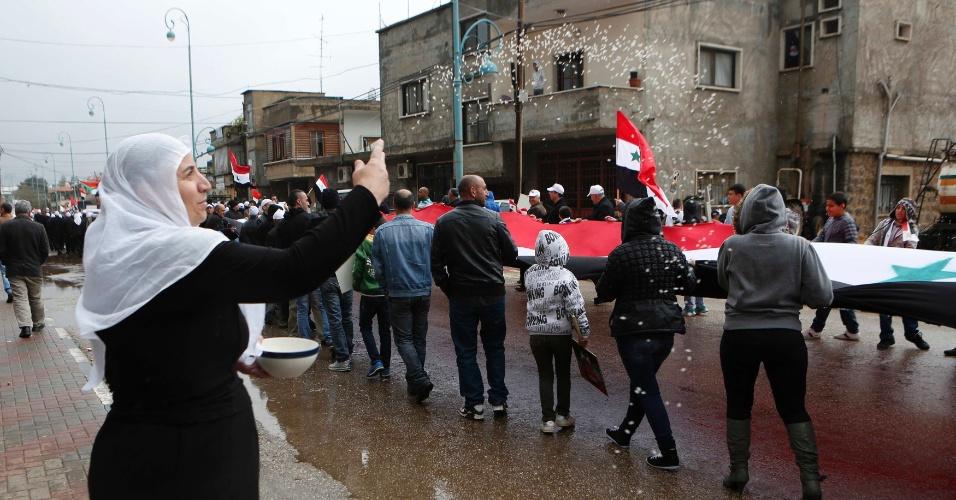 17.abr.2013 - Mulher joga arroz em membros da comunidade drusa que marcham segurando uma bandeira síria durante comemorações do Dia da Independência da Síria no vilarejo druso de Buqata. No dia 17 de abril de 1946, a Síria celebrou a retirada das últimas tropas francesas em seu território