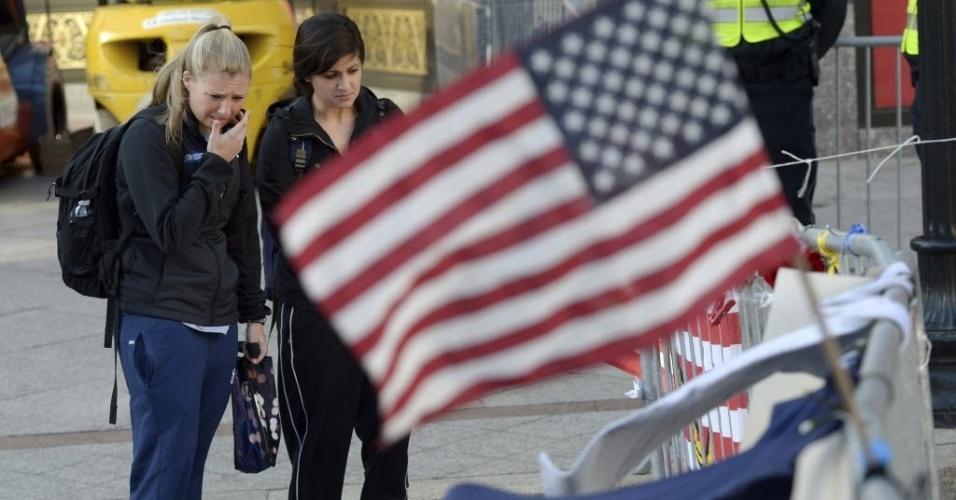 17.abr.2013 - Mulheres observam flores e bandeiras depositadas em avenida de Boston, Massachusetts, nos Estados Unidos, em memória das vítimas das explosões na Maratona de Boston