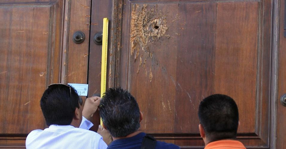 17.abr.2013 - Policiais mexicanos examinam entrada do jornal Mural, em Guadalajara, que foi atingida por uma granada, nesta quarta-feira (17). O México registrou 53 assassinatos a jornalistas em seis anos e é o país mais perigoso das Américas para a imprensa