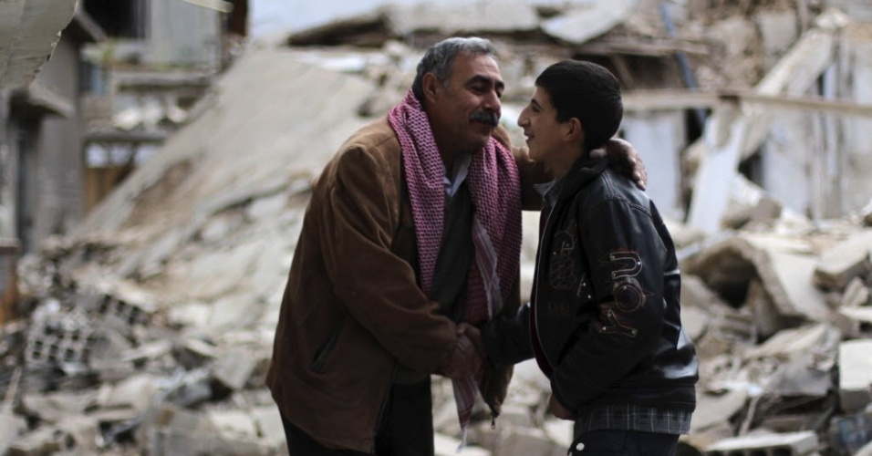 17.abr.2013 - Vizinhos se abraçam em frente a casas destruídas após atentados em Damasco, na Síria