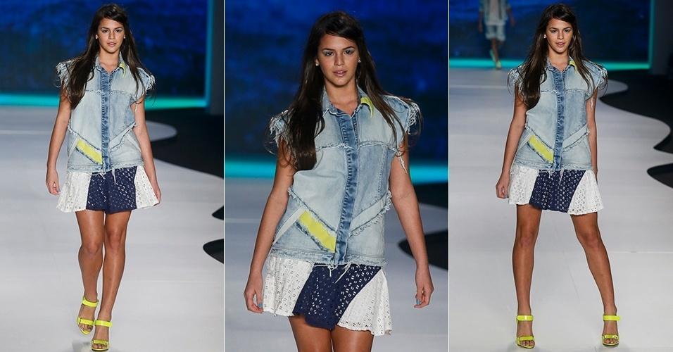 A atriz Bruna Marquezine abre o desfile da Coca-Cola Clothing para o Verão 2014 e,  desta vez, sem sustos! Seu look de entrada foi composto por camisa jeans sem mangas com recortes geométricos e saia branca com detalhe azul