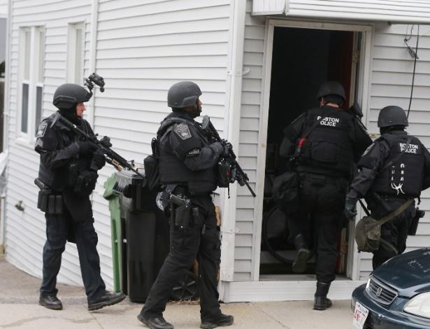 19.abr.2013 - Agentes da Swat, polícia de elite dos EUA, procuram um dos suspeitos dos atentados na Maratona de Boston, em Watertown, Massachusetts, nesta sexta-feira (19). O segundo suspeito, que ainda não foi identificado, foi morto após ser capturado pela polícia