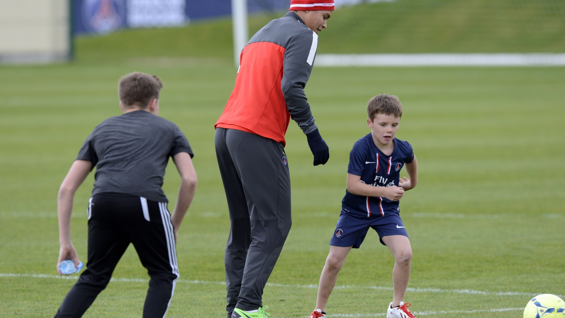 19.abr.2013 - Brooklyn Beckham (esq) e Cruz Beckham (dir), filhos do astro David Beckham, brincam com o zagueiro brasileiro Thiago Silva durante treino do Paris Saint-Germain