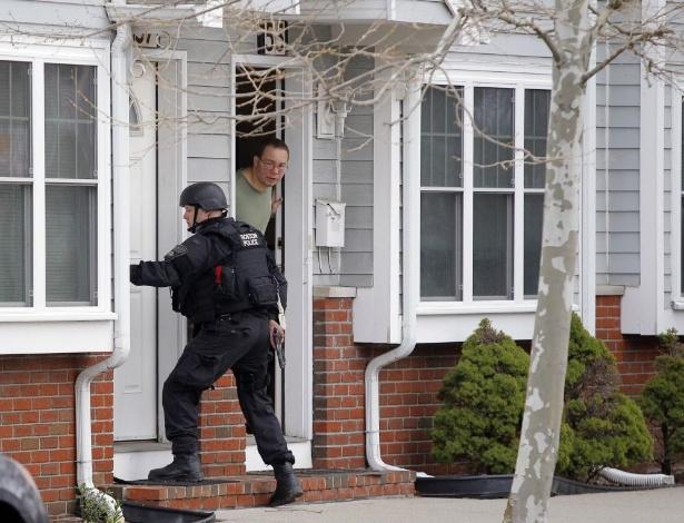 19.abr.2013 - Homem olha para fora de sua porta enquanto agente da Swat, polícia de elite dos EUA, procura um dos suspeitos dos atentados na Maratona de Boston, em Watertown, Massachusetts, nesta sexta-feira (19). O segundo suspeito, que ainda não foi identificado, foi morto após ser capturado pela polícia