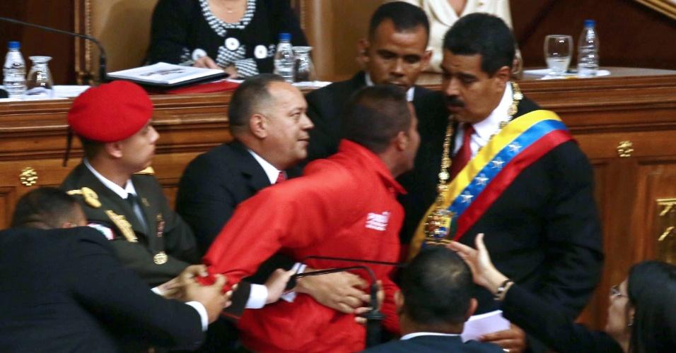 19.abr.2013 - O presidente da Assembleia Nacional da Venezuela, Diosdado Cabello, segura um homem (de vermelho) que chegou perto da tribuna e tirou o microfone do presidente Nicolás Maduro (à dir.), o que interrompeu por alguns minutos seu discurso de posse