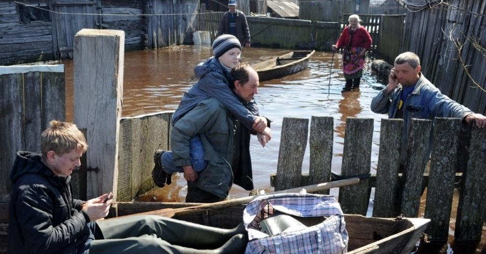 19.abr.2013 - Pessoas fazem chamadas telefônicas enquanto se preparam para evacuar seus parentes para um lugar seguro durante as enchentes em no vilarejo de Mordvin, a 310 km de Minsk, em Belarus