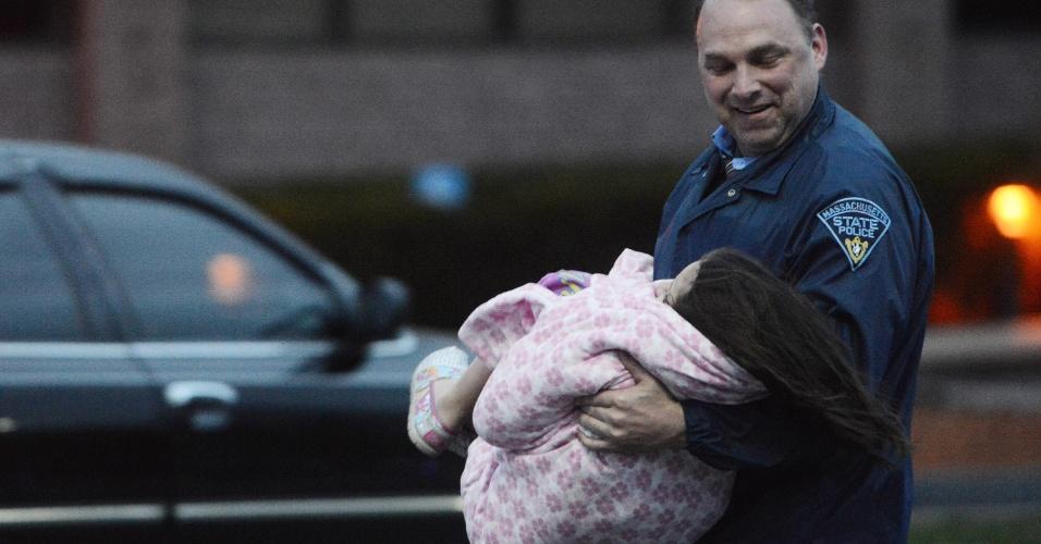 19.abr.2013 - Policial carrega criança durante evacuação de uma área onde um dos suspeitos do atentado em Boston estava escondido, em Watertown, cidade próxima a Boston (Estados Unidos). Dzhokhar Tsarnaev, 19, um dos suspeitos, foi preso na noite desta sexta-feira (19), segundo a polícia. Tamerlan Tsarnaev, 26, seu irmão, e também suspeito, morreu durante troca de tiros com a polícia na madrugada desta sexta-feira