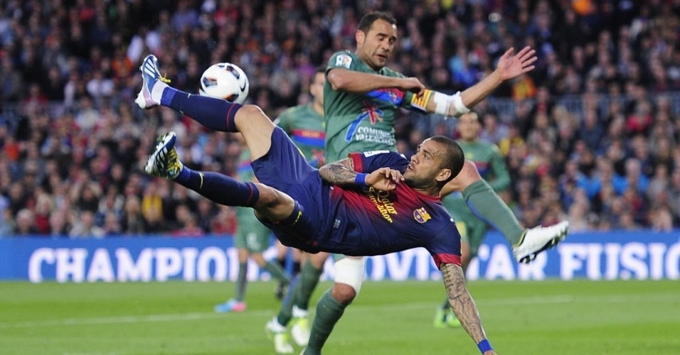 20.abr.2013 - Daniel Alves, lateral brasileiro do Barcelona, tenta a bicicleta diante da marcao de Juanfran Garcia, do Levante, em partida do Campeonato Espanhol