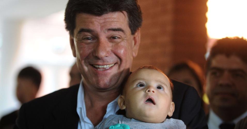 21.abr.2013 - Candidato do partido Liberal, Efraín Alegre, posa com bebê no colo, antes de votar em Assunção (Paraguai). Mais de três milhões de paraguaios vão às urnas neste domingo (21) nas sextas eleições realizadas desde a redemocratização no país, em 1989