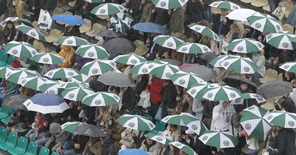 21.abr.2013 - Chuva atrapalha o início do jogo entre Novak Djokovic e Rafael Nadal em Monte Carlo e torcedores são obrigados a se proteger
