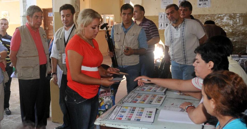 21.abr.2013 - Observadores da OEA (Organização dos Estados Americanos), chefiados por Oscar Arias (à esq.), inspecionam os trabalhos em uma mesa de votação de Assunção (Paraguai). O país realiza eleições presidenciais neste domingo (21)