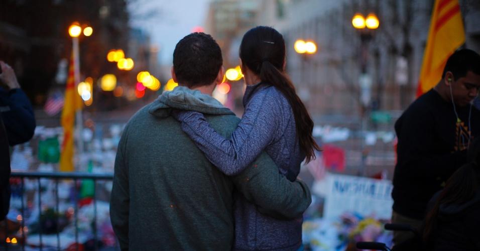 21.abr.2013 - Casal se abraça enquanto observa memorial em homenagem às vítimas do atentado na Maratona de Boston, na Boylston Streeton Boylston Street, em Boston, Massachusetts, na noite de domingo (21)
