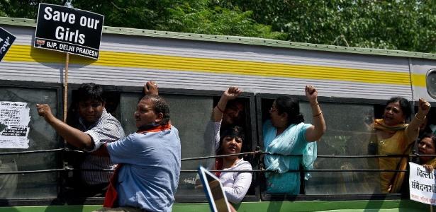 Com placas em punho e lotando um ônibus, manifestantes protestam contra o estupro de menina de 5 anos