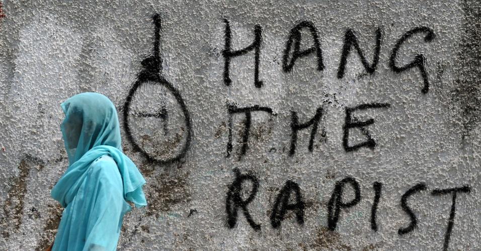 """22.abr.2013 - Mulher indiana passa por muro pichado com os dizeres """"enforquem o estuprador"""", em Nova Déli, nesta segunda-feira (22). Uma menina de cinco está hospitalizada após ter sido estuprada brutalmente durante dois dias. O caso gerou grandes protestos no país"""