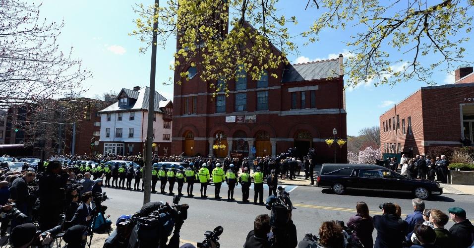 22.abr.2013 - Veículos de imprensa ficam do outro lado da rua da igreja de St. Joseph, em Medford, Massachusetts (EUA), atrás de uma linha formada pela Polícia de Medford, durante o funeral de Krystle Campbell, 29, uma das vítimas do atentado à bomba na Maratona de Boston, em 15 de abril
