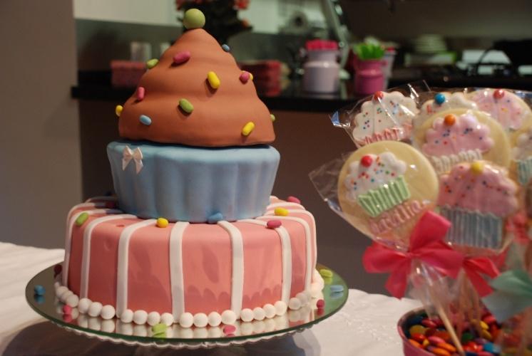 Como o tema da festa eram os Cupcakes, o bolo não poderia fugir à regra e imita um dos bolinhos da moda, mas bem maior e coberto de pasta americana. Este bolo de três andares foi feito pelo Atelier Paula Gradícola (www.paulagradicola.com.br)