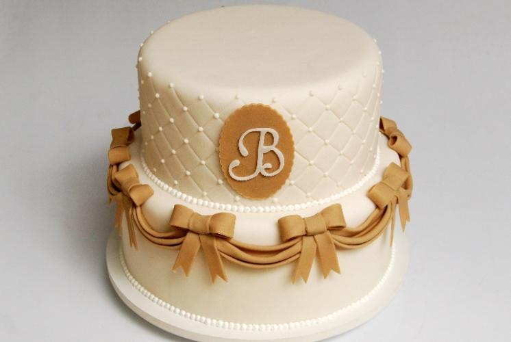 Nika Linden (www.nikalinden.com.br) sugere essa opção elegante e delicada de bolo. O primeiro andar é circundado por uma fita com laços e o segundo parece forrado com um tecido com acabamento capitonê