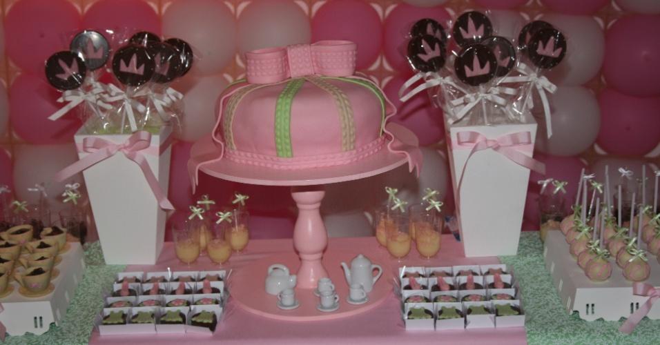 O bolo cor-de-rosa, que parece mais um presente, é uma criação da Divino Dolce (www.divinodolce.com.br). Até o laço foi feito com pasta americana e, portanto, é comestível. Para ter destaque na decoração festa, foi colocado sobre um pedestal, no centro da mesa