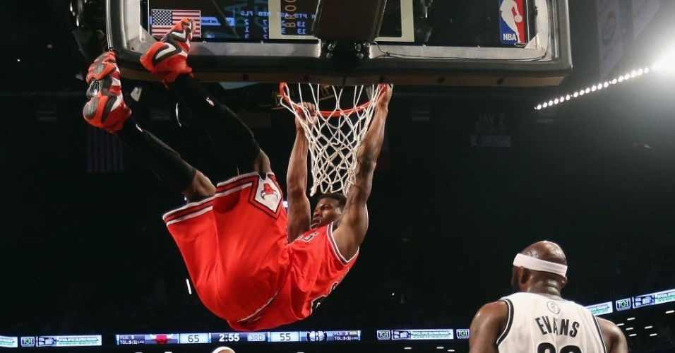 22.abr.2013 - O ala Jimmy Butler enterra a bola e faz pose no aro durante o triunfo do Chicago Bulls sobre o Brooklyn Nets pelos playoffs