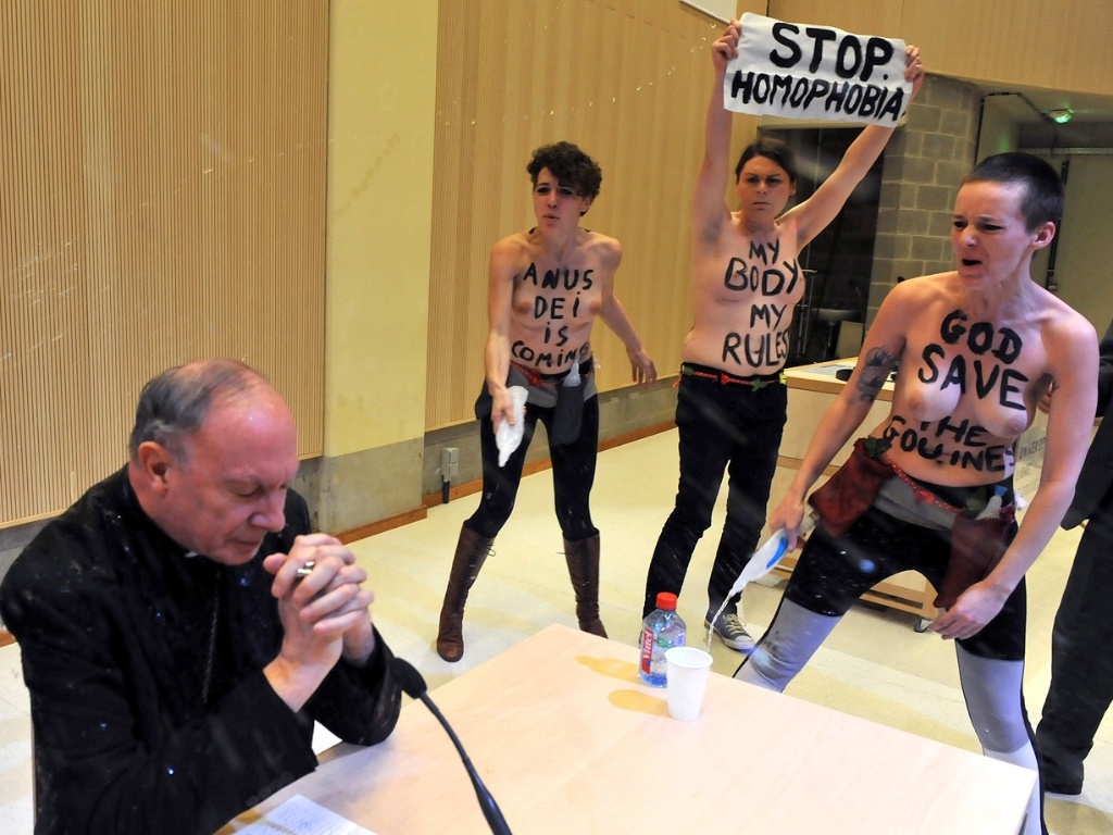 23.abr.2013 - Ativistas do grupo feminista Femen fazem um protesto contra a homofobia durante palestra do arcebispo Andre-Joseph Leonard ( esq.) em uma universidade de Bruxelas (Blgica)