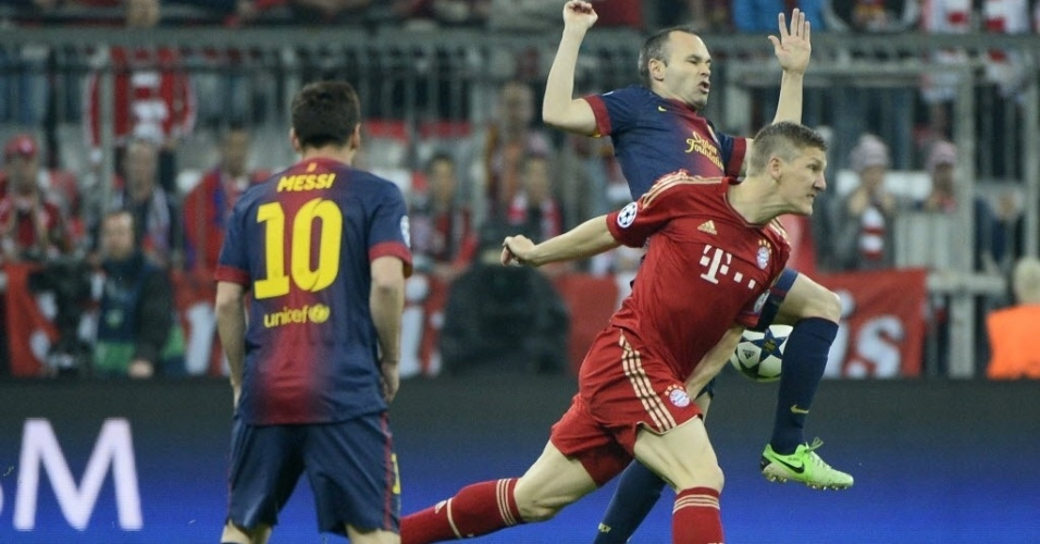 23.abr.2013 - Schweinsteiger e Iniesta disputam a bola durante a semifinal entre Bayern e Barcelona