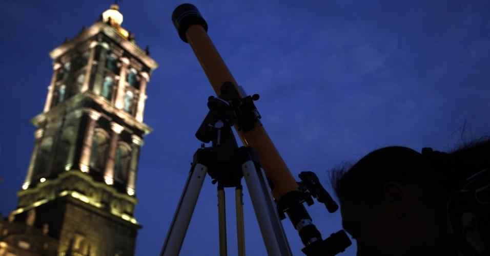 Jovem participa de evento no México, onde um grupo de 2.753 pessoas com telescópios tentam bater recorde mundial do maior número de observadores da Lua reunidos em um mesmo loca, em frente à catedral de Puebla