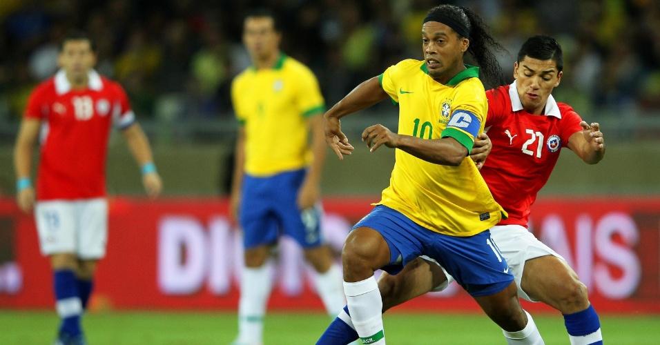 24.abr.2013 - Ronaldinho Gaúcho carrega a bola durante a partida entre Brasil e Chile, no Mineirão