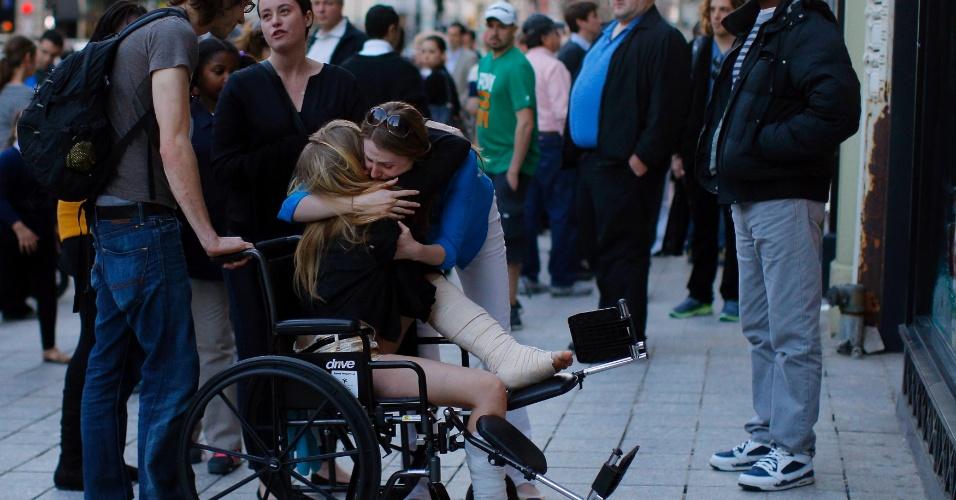 24.abr.2013 - Sobrevivente não identificada dos atentados na Maratona de Boston abraça amigos perto do local onde ocorreram as explosões em Boylston street em Boston, Massachusetts (EUA)