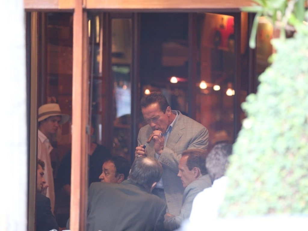 25.abr.2013 - Arnold Schwarzenegger fuma charuto em cafeteria na zona sul do Rio de Janeiro. O ator est na cidade para participar de um evento de fisiculturismo