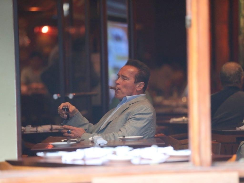 25.abr.2013 - Arnold Schwarzenegger fuma charuto em cafeteria na zona sul do Rio de Janeiro. O ator está na cidade para participar de um evento de fisiculturismo