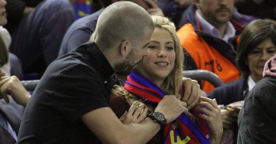 25.abr.2013 - Gerard Piqué, jogador do Barcelona, ajeita cachecol do time em volta do pescoço da namorada Shakira durante jogo de basquete entre Barcelona e Panathinaikos, em Barcelona. Os dois são pais do bebê Milan, de três meses