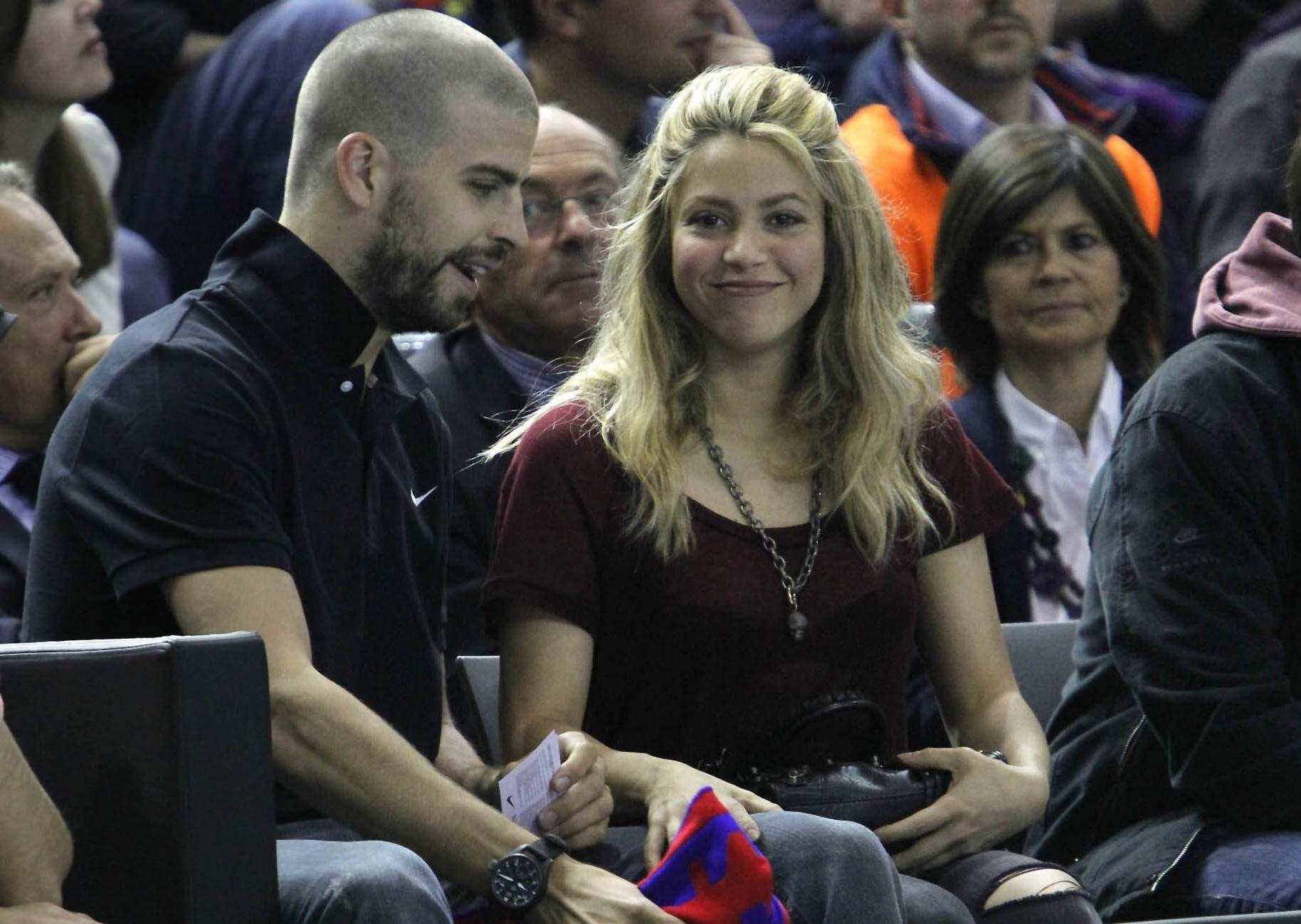 25.abr.2013 - Shakira sorri ao perceber que está sendo fotograda com o namorado Gerard Piqué durante jogo de basquete entre Barcelona e Panathinaikos, em Barcelona. Os dois são pais do bebê Milan, de três meses
