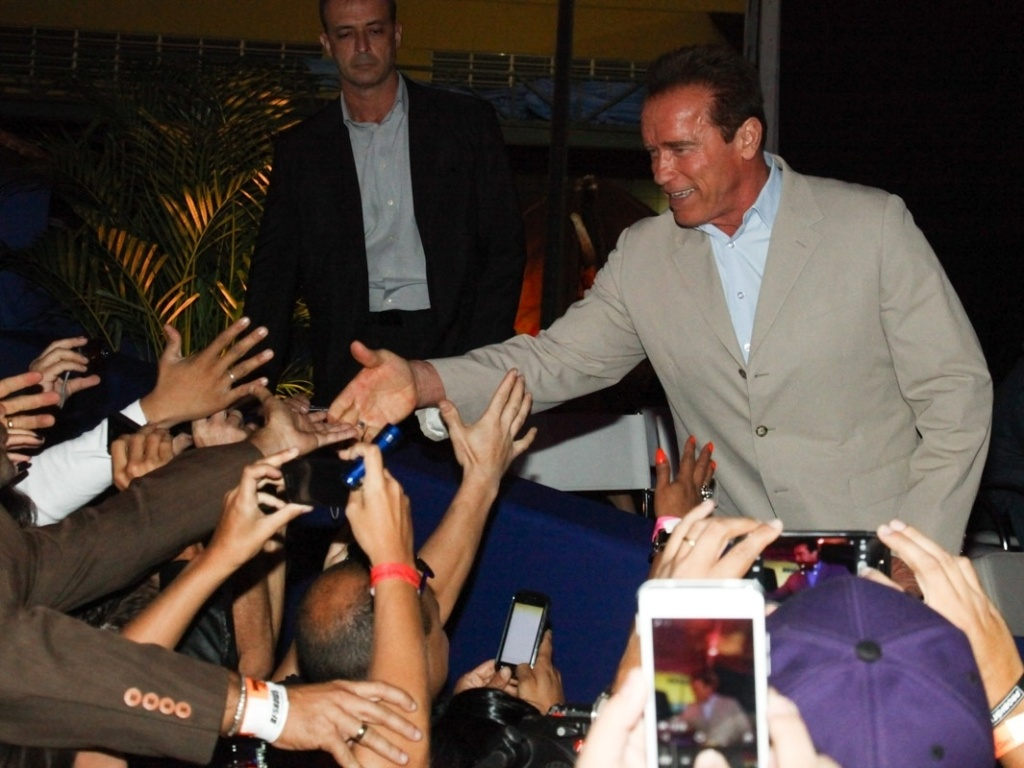 27.abr.2013 - O ator e ex-Governador da Califrnia Arnold Schwarzenegger cumprimenta fs na chegada  Cidade do Samba, no Rio, para mais eventos da Arnold Classic Brasil, feira de nutrio esportiva, lutas, performance e fitness