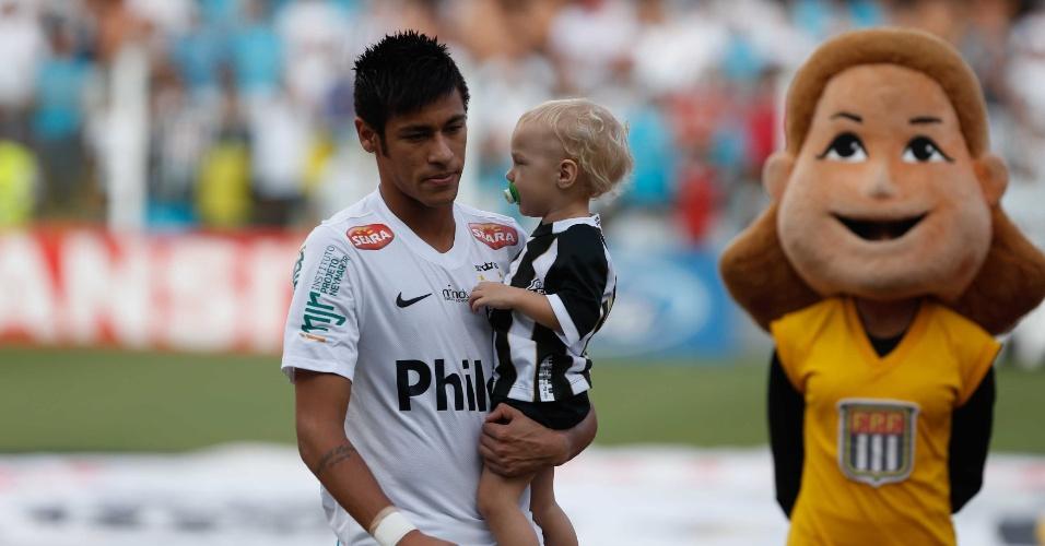 Neymar chega com o filho no colo para a partida contra o Palmeiras, pelas quartas do Paulistão